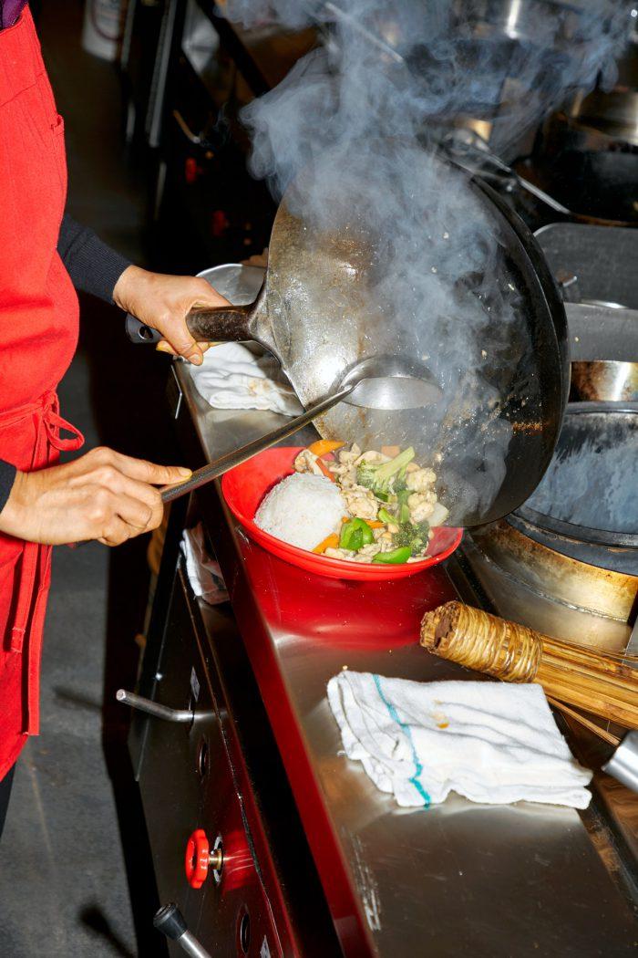 Photo d'un cuisinier qui dépose des légumes dans une assiette à partir d'un wok